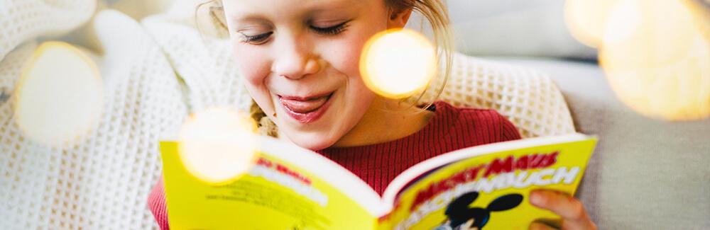 Ein fröhliches Mädchen liest Micky Maus Taschenbuch bei Egmont Publishing