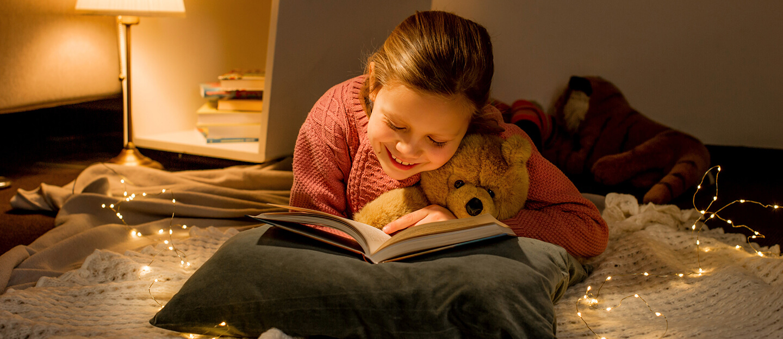 Ein kleines Mädchen liest in ihrem Bett ein Buch aus dem Verlag Egmont Publishing