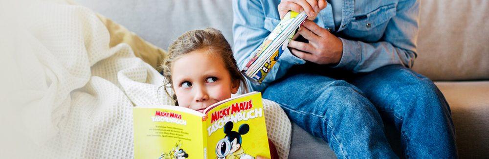 Ein Mädchen liest in einem Micky Maus Taschenbuch erschienen bei Egmont Publishing