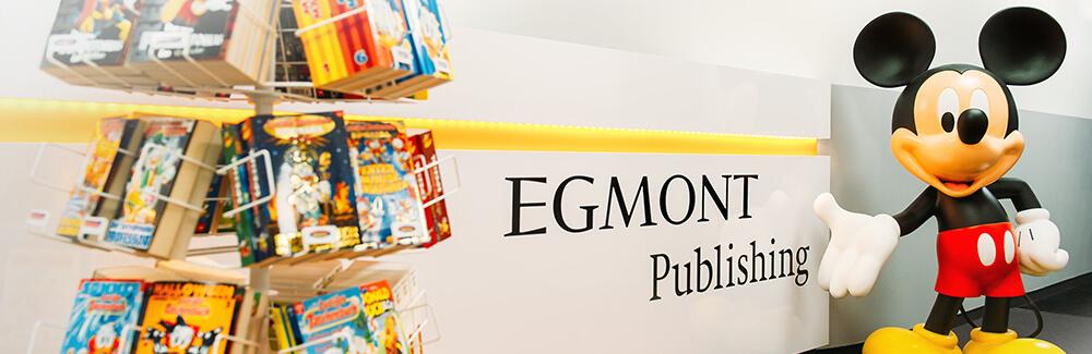 Eine Micky Maus Figur zeigt auf den Firmennamen Egmont Publishing an der Wand