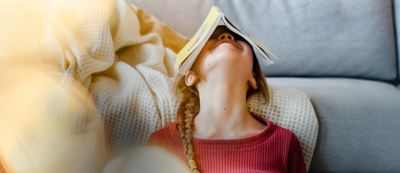Ein kleines Kind albert mit einem Taschenbuch aus dem Verlag Egmont Publishing herum